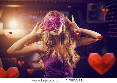 Woman with masquerade dancing on dance floor against hearts
