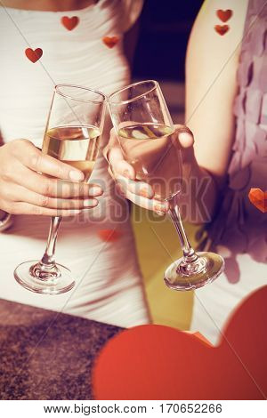 Cropped image of women toasting champagne flute against love heart pattern