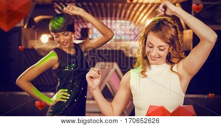 Smiling female friends dancing on dance floor against hearts