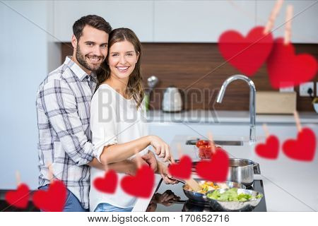 Composite image of hanging red heart and couple cooking food in kitchen