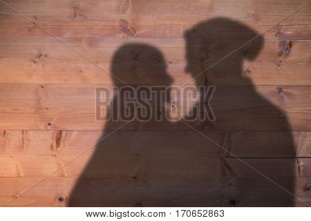 Happy couple holding paper heart against bleached wooden planks background