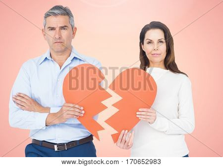 Upset couple holding broken heart against pink background
