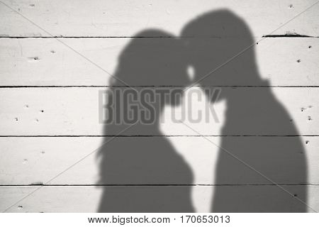 Young couple rubbing nose against white wood