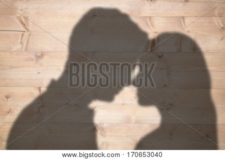 Couple standing head against head against bleached wooden planks background