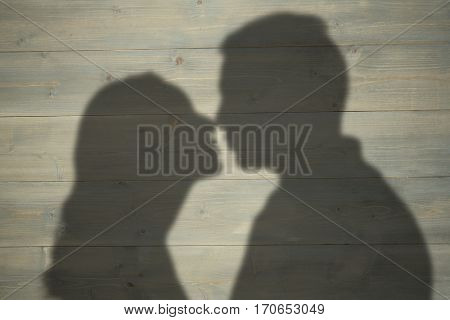 Profile view of couple about to kiss against bleached wooden planks background