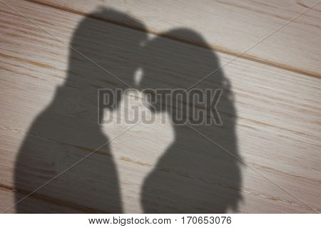 Happy young couple rubbing nose against brown wooden background