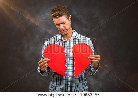 Sad man holding a broken card against grey