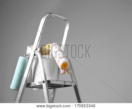 Ladder and set of tools for repair on grey background