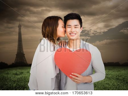 Woman kissing man while holding heart with digitally generated Eifel tower in background