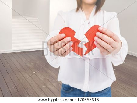 Mid-section of woman holding broken hearts at home