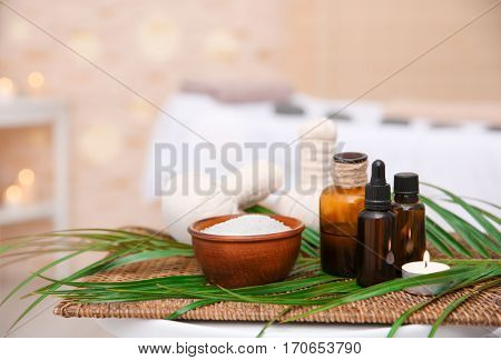Massage setting with natural oil and herbal compress balls on wicker mat