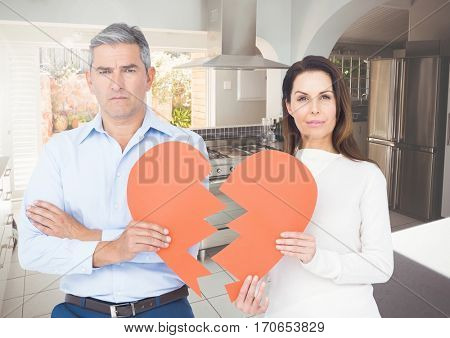 Portrait of sad couple holding broken hearts at home