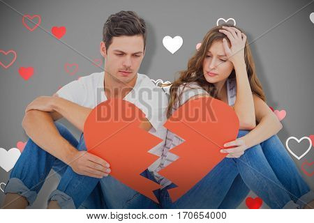 Young couple sitting on floor with broken heart shape paper against grey background