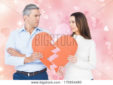 Sad couple looking each other while holding broken hearts against digital composite heart background