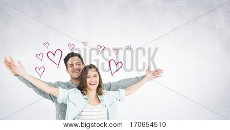 Portrait of couple standing with arms outstretched against digitally generated heart background