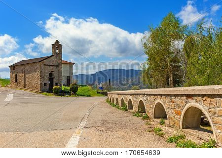 Low stone fence along road towards small parish church under blue sky in Piedmont, Northern Italy.