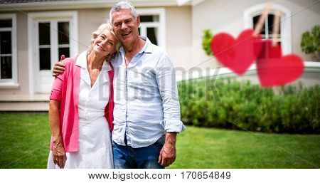 Hearts hanging on a line against senior couple with arms around standing in yard