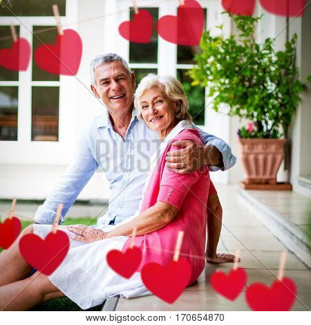 Hearts hanging on a line against portrait of senior couple sitting in yard