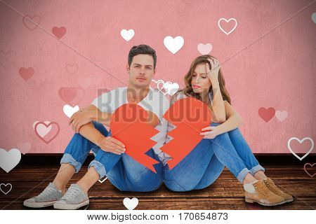 Young couple sitting on floor with broken heart shape paper against white background