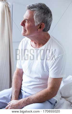 Thoughtful senior man sitting on bed in bedroom at home