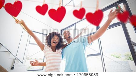 Hearts hanging on a line against excited young couple in their new home
