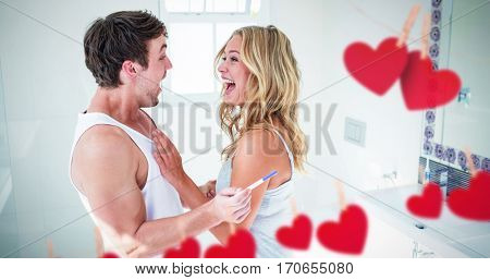 Hearts hanging on a line against happy couple being excited with positive pregnancy test