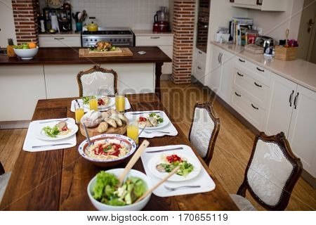 Dinning table laid with meal in kitchen