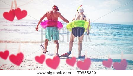 Hearts hanging on a line against senior couple in inflatable ring and flipper walking at beach