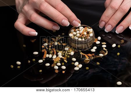 Female hands with beautiful classical French manicure gather the haricot scattered on a black background, peas, dried vegetables and spices in a vintage melkhiorovy saltcellar