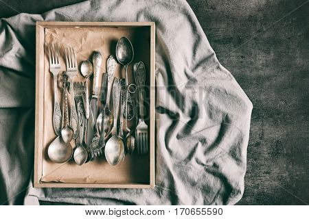 Set of silverware in wooden box on grey background