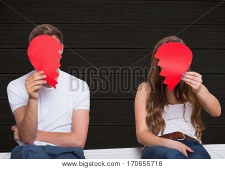 Sad couple hiding their face with broken hearts against wooden background