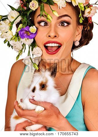 Easter girl holding bunny. Woman with holiday spring flowers hairstyle and make up with fake eyelashes. Female makes squint eye for fun. She has strabismus on white background.