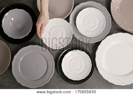 Female hand with saucer and dishware on grey background