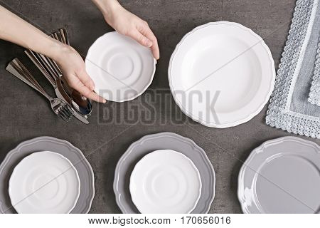 Female hands with saucer and dishware on grey background