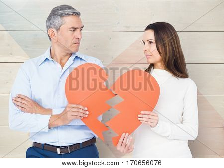 Sad couple looking each other while holding broken hearts against wooden background