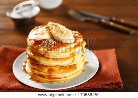 Delicious pancakes with maple syrup and sliced banana on wooden table