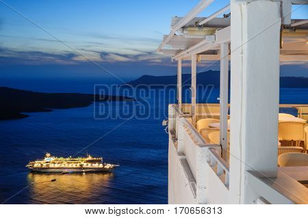 Enlighted cruise ship just after sunset near Fira town at Santorini island, Greece, empty outdoor cafe to the right and caldera sea at background