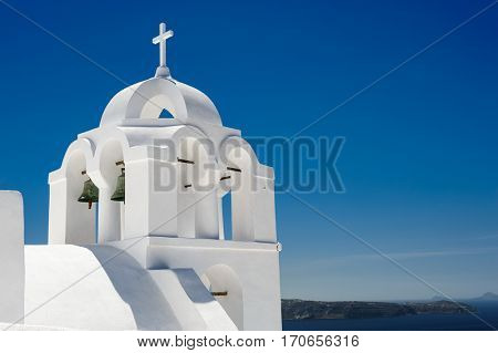White orthodox church with bell tower. Fira, Santorini Greece. Copyspace