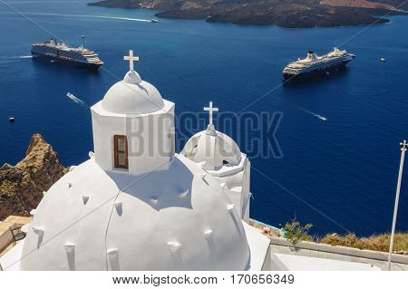 White orthodox church bell tower and sea with ships at background. Fira, Santorini Greece. Copyspace