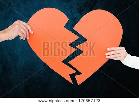 Hand of couple holding broken hearts against blue background
