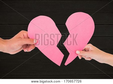 Hands of couple holding broken heart against wooden background