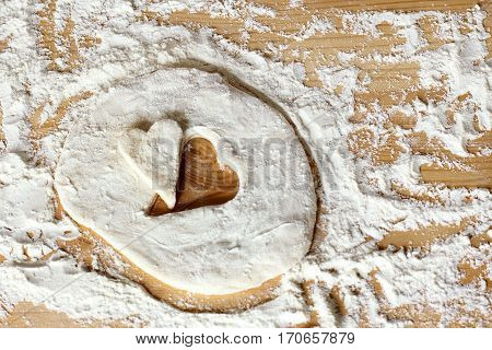blank heart shape of farinaceous dough on a wooden table / cooking pastry for the holiday
