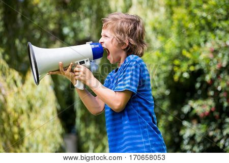 A little boy is screaming with a megaphone on a park