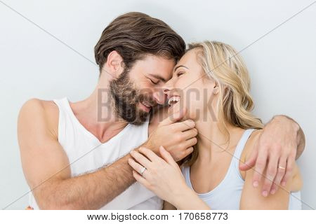 Romantic couple embracing on bed in bedroom