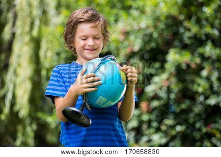A little boy is holding a globe in his hands