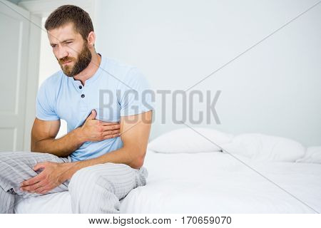 Young man having chest pain on bed in bedroom
