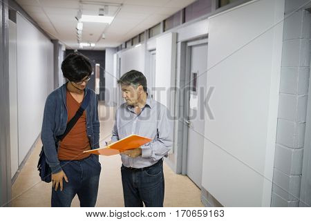 Professor with notebook talking to a student in corridor