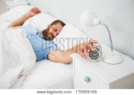 Sleeping man awakened by a alarm on bed at bedroom