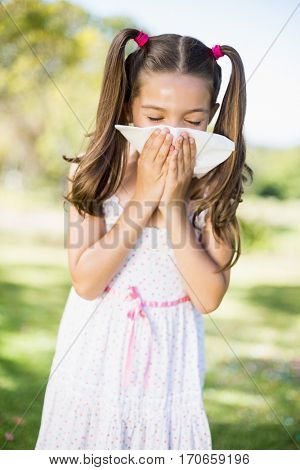 Girl blowing her nose with handkerchief while sneezing in the park