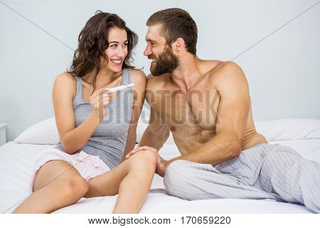 Happy couple looking at pregnancy test on bed at bedroom